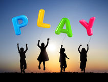 Children Holding Balloons with Word Play. Little Children Jumping and Holding Balloons that Forms Play Stock Photo