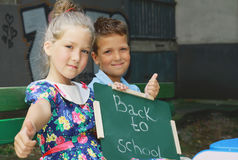 Children holding Chalkboard with words Back to School. Outdoor photo. Education and kids fashion concept Stock Image