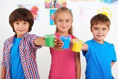 Children holding colorful cans with paint Stock Photography