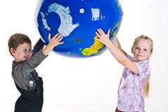 Children Holding The Earth. Smiling young boy and girl holding a large replica of the earth over their heads.  Isolated on a white background Royalty Free Stock Photography