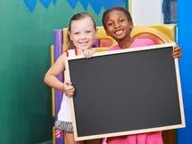 Children holding empty chalkboard in preschool stock photos