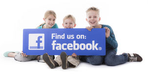 Children holding Facebook find us sign Stock Photo