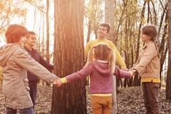 Children holding hands around a tree. stock images