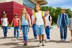 Children holding hands carry rucksacks and walk Stock Photo