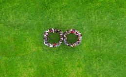 Children holding hands in circle. Green meadow scene, aerial view royalty free stock image