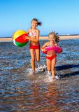 Children holding hands running on  beach Stock Photos