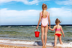 Children holding hands walking on the beach. Royalty Free Stock Image