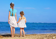 Children holding hands walking on the beach. Royalty Free Stock Images