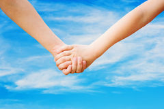 Children holding his hand in summer park outdoor, ag. Close up of children holding his hand in summer park outdoor, against the blue sky Royalty Free Stock Images