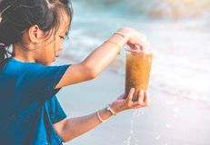 Children holding Plastic bottle that he found on the beach for enviromental clean up concept royalty free stock photo