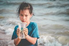 Children holding Plastic cup that he found on the beach for enviromental clean up concept stock photos