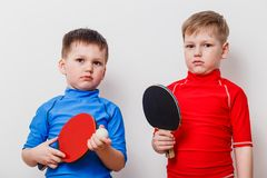 The children are holding the racket for table tennis. On white background stock photo