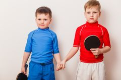 The children are holding the racket for table tennis on white background. Two children are holding the racket for table tennis on white background stock image