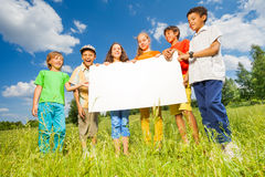Children holding rectangular shape paper together Stock Image