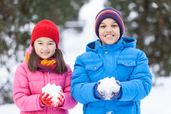 Children holding snowballs and looking happy. Royalty Free Stock Photos