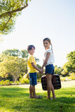 Children holding their hands looking back while holding a luggage Royalty Free Stock Photo
