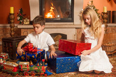 Children with holiday gifts by fireplace Royalty Free Stock Photography