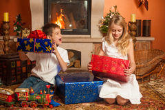 Children with holiday gifts by fireplace Stock Photo