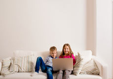 Children at home sitting on sofa, playing with laptop Royalty Free Stock Images
