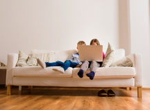 Children at home sitting on sofa, playing with laptop Stock Photos