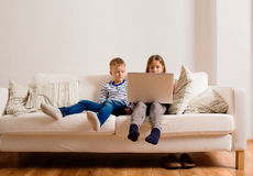 Children at home sitting on sofa, playing with laptop Royalty Free Stock Photography