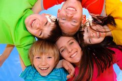 Children hugging. Happy children hugging in a circle against blue sky Royalty Free Stock Photos