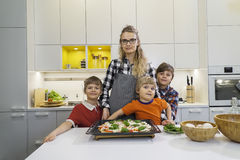 Children hugging mother in the kitchen. Three boys children hugging mother in the kitchen, preparing pizza Royalty Free Stock Photography