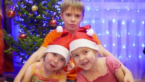 Children hugging and smiling at Christmas party. In the background, lights and garlands of Christmas fir. Children hugging and smiling at Christmas eve stock video footage