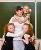 Children hugging their teacher Royalty Free Stock Photos