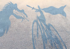 Children imagination. Concept with cast shadows on a gravel floor of a superhero child wearing a cape on a bicycle slaying an imaginary dragon as a metaphor for royalty free illustration