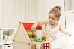 Children imagination or creativity concept. Cute little girl playing with dollhouse. Family house concept - Portrait of little girl with house model. Investment Royalty Free Stock Photography