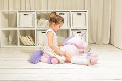Children imagination or creativity concept. Cute little girl riding on a pink pony toy. Children imagination or creativity concept. Princess and Fairy tale royalty free stock photo