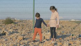 Children of immigrants wait at the border to continue their journey. high fence barbed wire on the rocky shore stock video footage