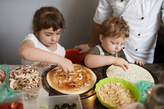 Children impose  ingredients for pizza Royalty Free Stock Photos