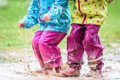 Children In Rubber Boots And Rain Clothes Jumping In Puddle. Stock Photography
