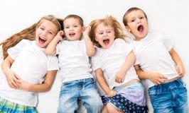 Children In White Shirts Lying On The Floor Stock Photo