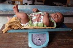 Children in India. May 03, 2011-ThakurPukur,Kolkata, West Bengal,India -A child on the weight machine in the clinic center of Kolkata Royalty Free Stock Photo