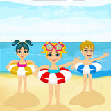 Children with inflatable rings standing on the beach Stock Photos