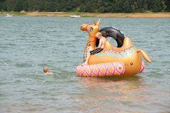Children on the inflatable toy on the lake stock photo