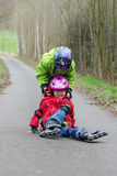Children on inline skates. An older brother helping his younger sister to stand back Stock Image