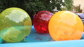 Children inside the balls on water stock footage