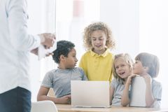 Children integrating during extra-curricular classes. Multicultural group of children integrating during extra-curricular computer classes royalty free stock images