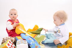Children with a jacket sit in a heap of toys Royalty Free Stock Images