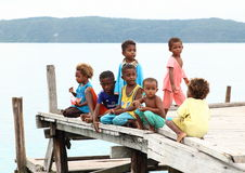 Children on jetty. Little boys and girls - Papuan children on jetty of a small harbor on island Mansuar (Raja Ampat, Papua Barat, Indonesia royalty free stock photos