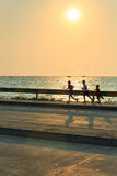 Children jogging alongside the sea Stock Images