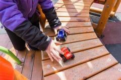 Children& x27; juegos al aire libre de s en el patio Pequeños carros en niño Fotos de archivo