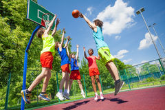 Children jump for ball during basketball game Stock Photo