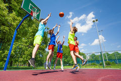 Children jump for flying ball during basketball Stock Photos