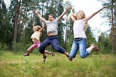 Children jump on lawn in summer forest Royalty Free Stock Photography
