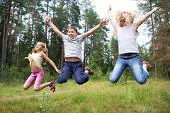 Children jump on lawn in summer forest. And enjoy life in sports Stock Photography